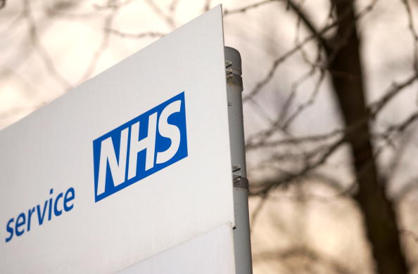 An NHS sign next to some trees